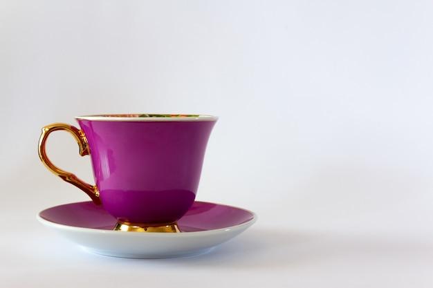 Różowy kubek herbaty lub kawy ze złotym wykończeniem na białym tle. selektywne skupienie. skopiuj miejsce.
