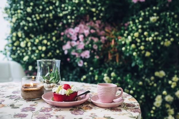 Różowy kubek i talerz z ciastem stoi okrągły stół przed ścianą w