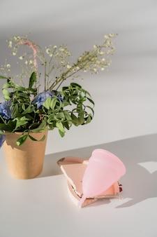 Różowy kubek menstruacyjny na białym tle ze światłem słonecznym i cieniami.