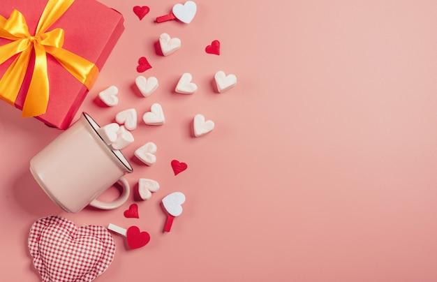 Różowy kubek na różowej powierzchni wypełnionej piankami w kształcie serc. obok jest pudełko z prezentem na walentynki. v