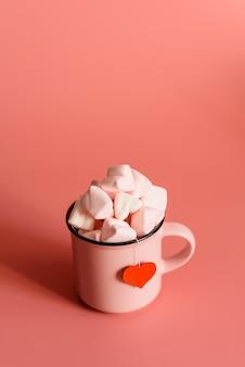 Różowy kubek na różowej powierzchni wypełnionej piankami w kształcie serc.
