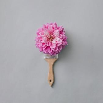 Różowy kwiat dalii pokrywający włosie pędzla z drewnianym uchwytem poniżej w koncepcji kreatywności, wystroju wnętrz, majsterkowania lub renowacji na szarym tle