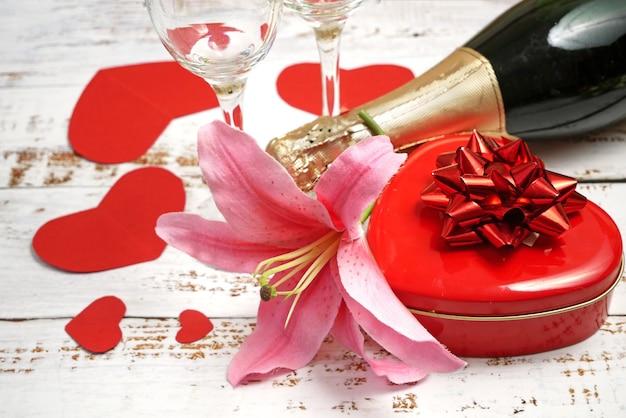 Różowy kwiat lilii, czerwone pudełko w kształcie serca z kokardką, butelka szampana i dwie szklanki