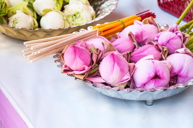 Różowy kwiat lotosu, kadzidełka i świece ustawione do modlitwy buddy w świątyni