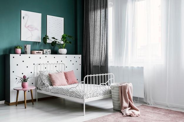 Różowy kwiat na stole obok białego łóżka w jasnym wnętrzu sypialni z plakatami na zielonej ścianie