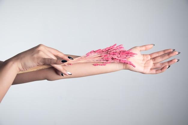 Różowy kwiat w kobiecej dłoni z manicure
