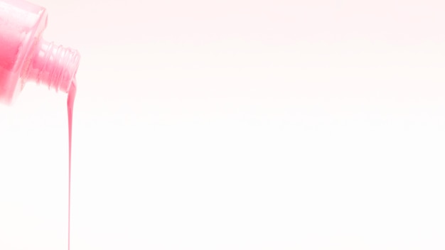 Różowy lakier do paznokci leje na białym tle