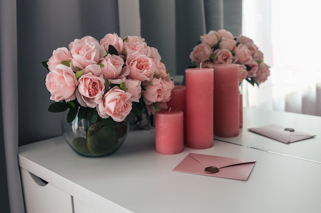 Różowy list na kobiecym pulpicie, bukiet róż i świece.