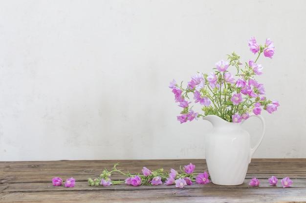 Różowy malwa w białym dzbanku na białym tle