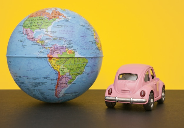 Różowy mały samochód retro ze świata kuli ziemskiej.