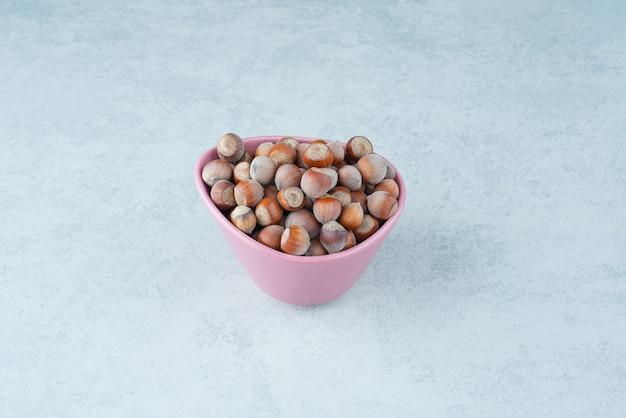 Różowy mały talerz pełen orzechów na tle marmuru. wysokiej jakości zdjęcie