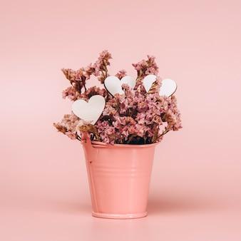 Różowy metalowy kosz z naturalnymi kwiatami i drewnianymi serduszkami na różowej ścianie.
