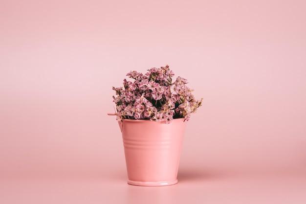 Różowy metalowy kosz z naturalnymi kwiatami
