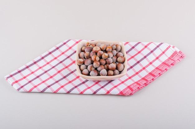 Różowy miska łuskanych orzechów laskowych organicznych umieszczonych na białym tle. zdjęcie wysokiej jakości