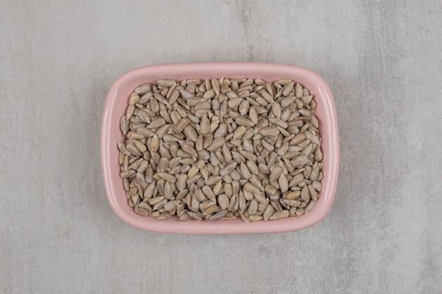 Różowy miska prażonych nasion słonecznika na marmurowym tle.