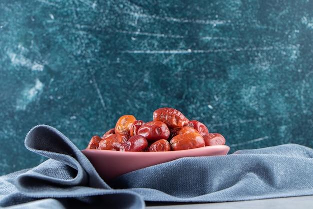 Różowy miska smaczne dojrzałe srebrne jagody na marmurowym tle.