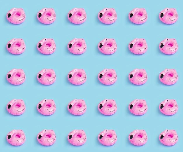 Różowy nadmuchiwany wzór flaminga na niebieskiej ścianie. letnie wakacje, koncepcja wakacji nad morzem
