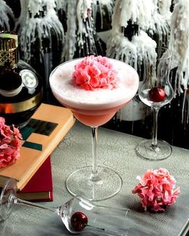 Różowy napój z pianką w szklance i różowe kwiaty na nim