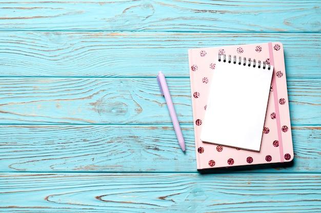 Różowy notatnik z piórem na niebieskim tle drewnianych. miejsce na tekst. widok z góry.