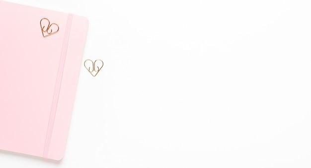 Różowy notatnik żeński ze złotymi spinaczami gwiazd na białym tle. skopiuj przestrzeń, widok z góry, płaski układ.