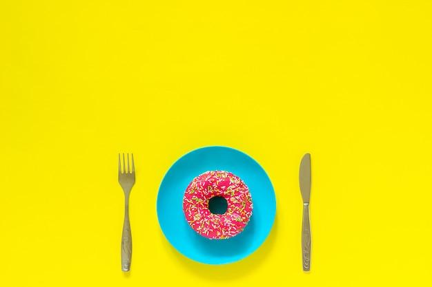 Różowy pączek na rozwidleniu noża niebieski talerz i sztućce na żółtym tle.