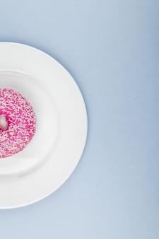 Różowy pączek z posypką na białym talerzu
