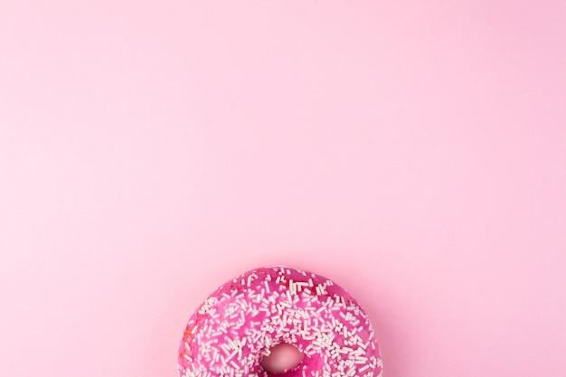 Różowy pączek z posypką na różowej powierzchni