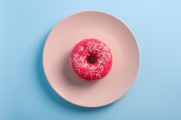 Różowy pączek z posypką na różowym talerzu, słodko glazurowany deser na niebieskim minimal