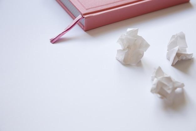 Różowy pamiętnik na białym tle i pogniecione kartki papieru. błędy w liście