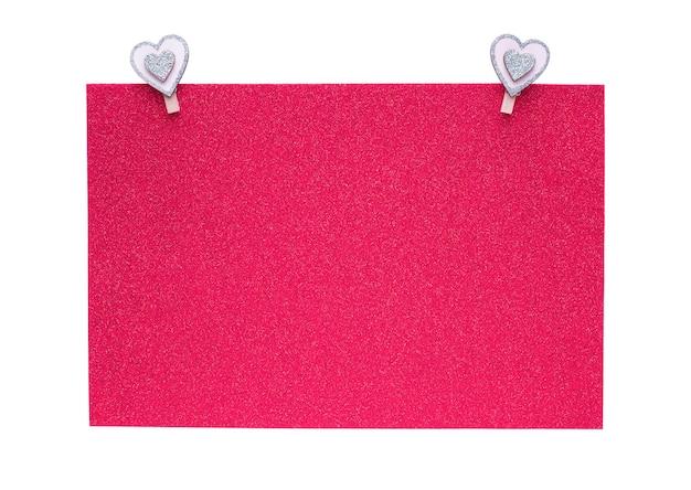 Różowy papier brokatowy z klipsami w kształcie serca na białym tle