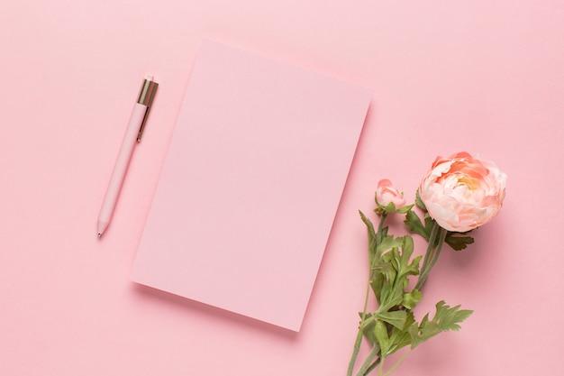 Różowy papier z długopisem i kwiatami
