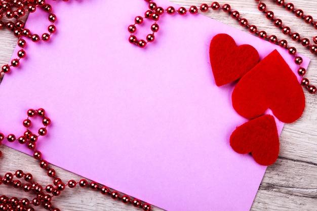 Różowy papier z girlandą z koralików. tkanina serca i karta. podziel się radością na wakacjach. pozdrów rodzinę i przyjaciół.