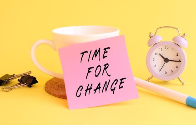 Różowy papier z napisem czas na zmianę na białym kubku