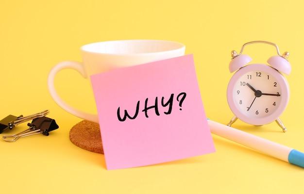 Różowy papier z napisem dlaczego na białym kubku pióro zegara na żółtym tle