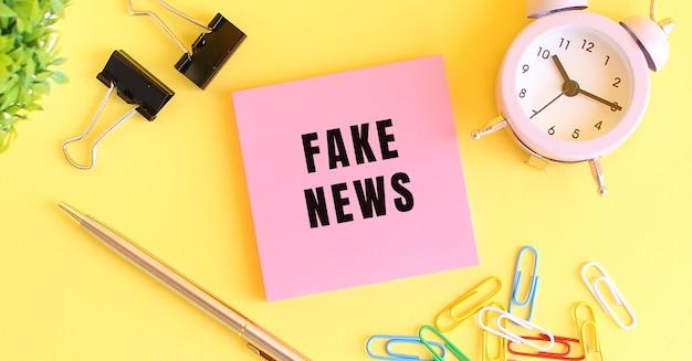 Różowy papier z napisem fake news długopis z zegarem na żółtym tle