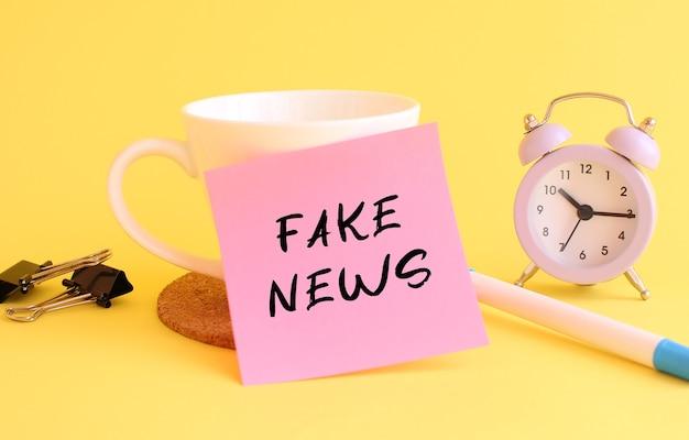 Różowy papier z napisem fake news na białym kubku. zegar, długopis na żółtym tle.