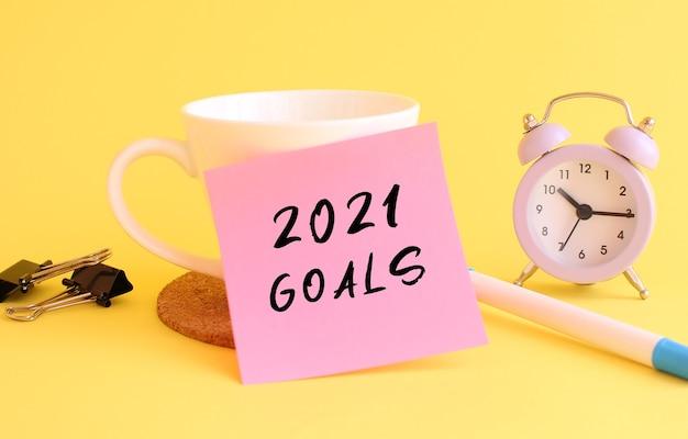 Różowy papier z napisem goals 2021 na białym kubku. żółte tło. zarys projektu.