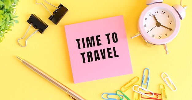 Różowy papier z napisem time to travel. zegar, długopis na żółtym tle. zarys projektu.