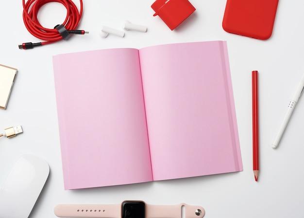 Różowy papierowy notatnik, power bank z kablem, czerwony smartfon, słuchawki, bezprzewodowa mysz i inteligentny zegarek