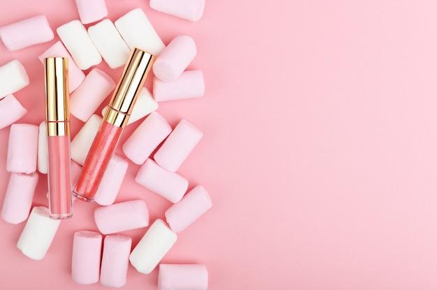 Różowy pastelowy błyszczyk na tle słodyczy.