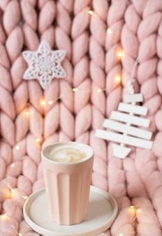 Różowy pastelowy wełniany gigantyczny koc z merynosów, piernikowy kubek, filiżanka z cappuccino, świąteczna zabawka, nowy rok, światła