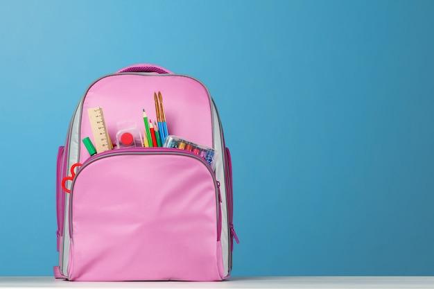 Różowy plecak z artykułami biurowymi na stole.