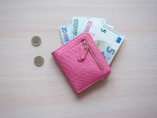 Różowy portfel i banknoty euro. widok z góry.