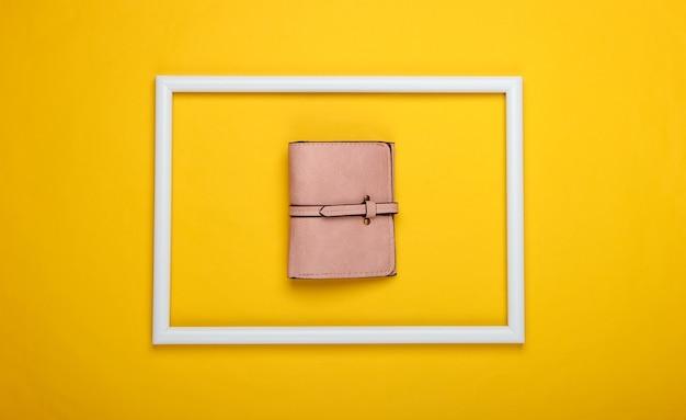 Różowy portfel w białej ramce na żółtej powierzchni