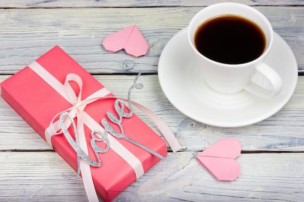 Różowy prezent, filiżanka kawy, napis love i papierowe serca na jasnym drewnianym stole. styl prowansalski.