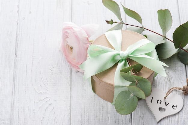 Różowy ranunculus i pudełko z zieloną wstążką