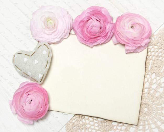 Różowy ranunculus kwitnie i papierowej kopii przestrzeni ściana na szydełkowym serwetka odgórnym widoku