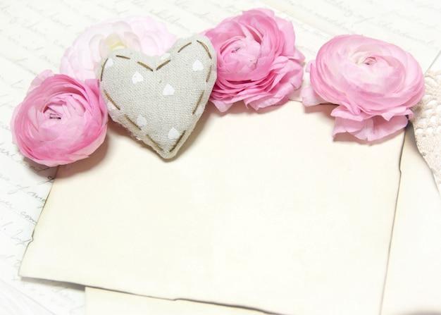 Różowy ranunculus kwitnie, tkaniny serce i papierowej kopii przestrzeni ściana na szydełkowym serwetka zakończeniu up