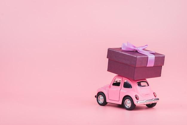 Różowy retro samochodzik dostarcza pudełko na różowym tle. pocztówka z 14 lutego, walentynki. dostawa kwiatów. dzień kobiet