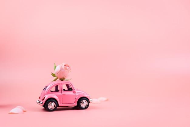 Różowy retro samochodzik dostarcza różowy kwiat na różowym tle. pocztówka z 14 lutego, walentynki. 8 marca, międzynarodowy dzień kobiet